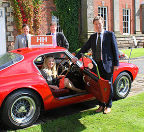 Trish Ashton from Hale Barnes, tries out the 1960 Ferrari Berlinetta watched by  (L to R): Nick Delaney, business development manager, H&H Classics, Crispin Harris, director Jackson Stops and Staff and Simon Hope, managing director, H&H Classics.