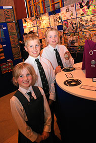 Siblings,(L-R) Evelyn, George and Helen (displaying her metal brooch exhibit) who are all pupils at Terra Nova.