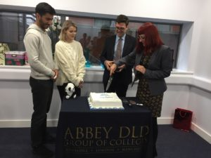 L-R Students Jehaad Khalid (18) and Lara O'Donoghue (18) with Mayor of Greater Manchester Andy Burnham and Principal of Abbey College Manchester Liz Elam cutting the cake.