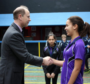 Hannah Wall (13) receives a medal from HRH The Earl of Wessex as fellow Manchester High pupil Iman Sheen (14) from Didsbury watches on