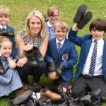 Caroline Johnson is pictured with junior pupils and their shoes.