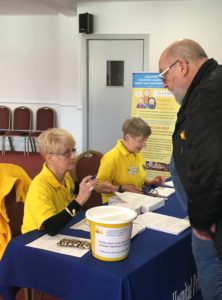 Volunteers Maureen and Wendy checking people in for their blood test.